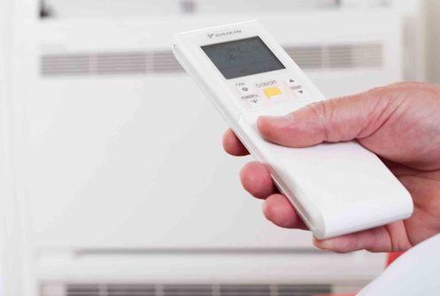 Hand mit Fernbedienung und Klimaanlage