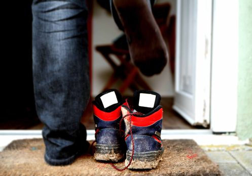Monteur zieht schmutzige Schuhe aus